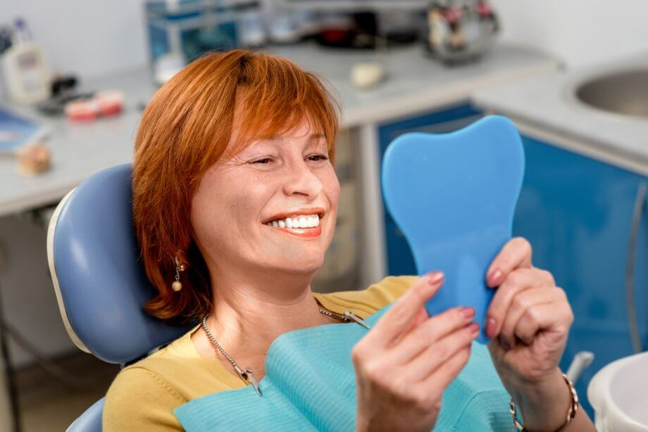 woman examining teeth at dentist